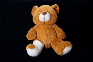 Teddy bear with a leg injury, sitting on a black sofa.